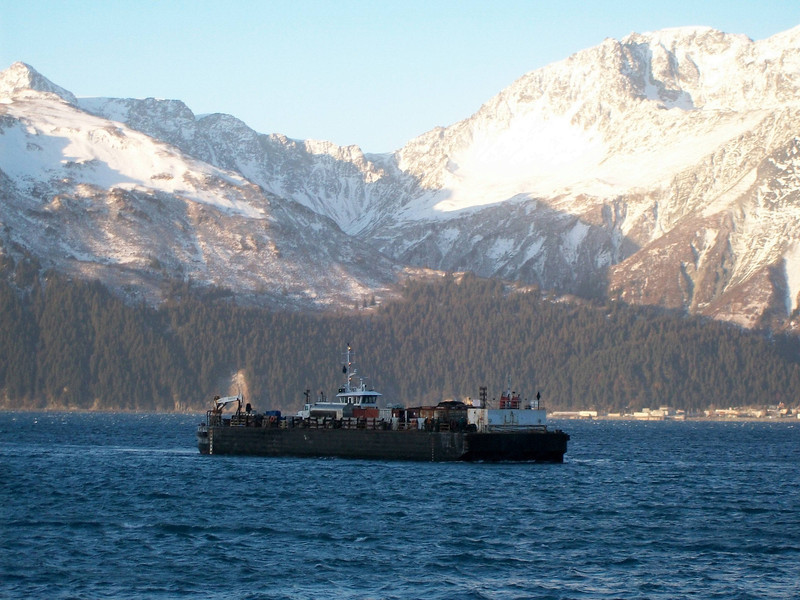 In Resurrection Bay. The town of Seward is behind to the right, but the pier is from the viewers perspective. That is, the barge is being pushed toward us by the two tugboats, with the strong and gusty winds coming from the right of the picture.