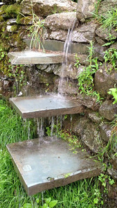 Movie of rainwater pouring over slate steps, like a waterfall. Hiking to Wansfell Pike, Ambleside, Lakes District, England.