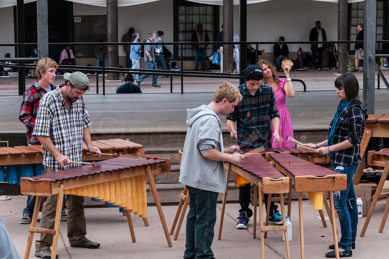 A large marimba ensemble, 'Polyphony Marimba' playing on the Plaza. Peter Swing in the green hat and his Wife, Raven Swing in the background.
