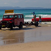 Dive boat recovery in progress on Byron Beach. The boat capsized offshore, drifted to the beach, and was flipped and recovered by the crew and a hefty old Land Cruiser.