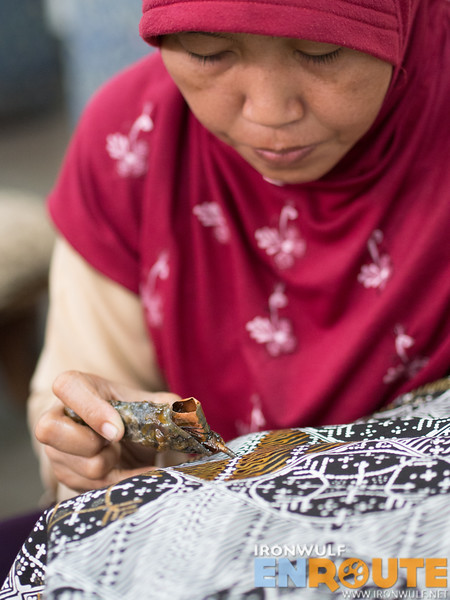 A lady carefully applying wax on a pattern of a fabric