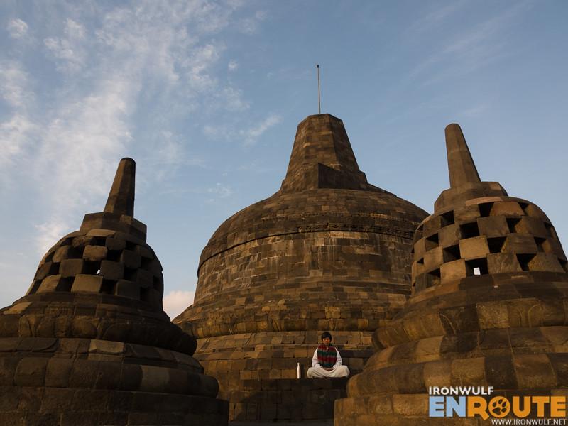 A woman meditating at the top stupa