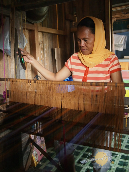 A weaver doing her work in her house in Bulalo