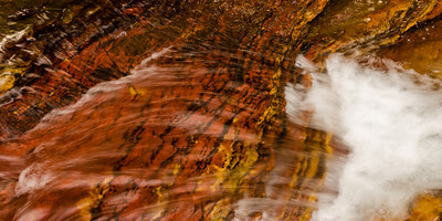 The waters of St. Mary Creek running over richly covered sedimentary rocks.
