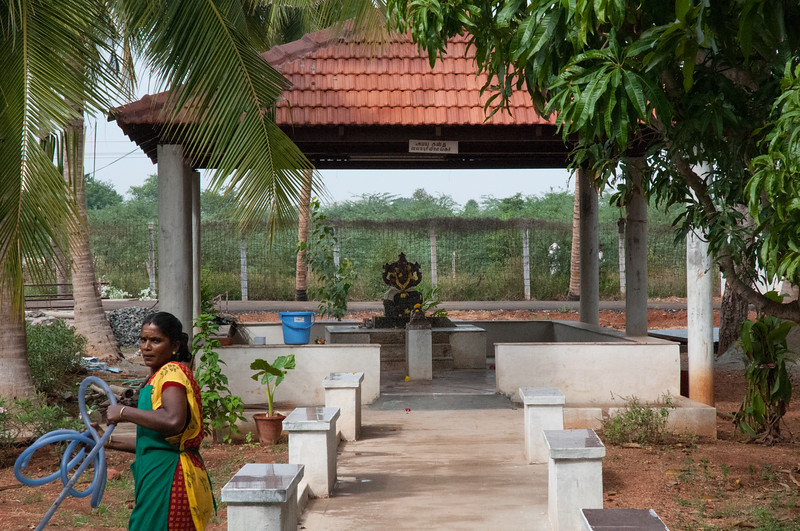 There is a small temple for residents. Note that the garden worker wears a sari and apron.