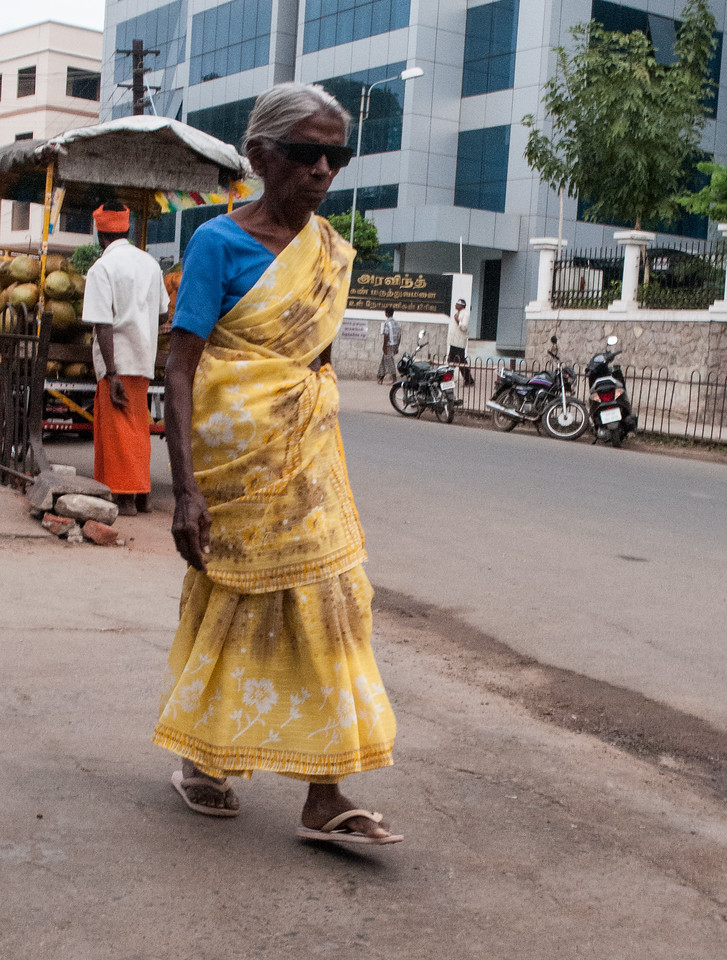 A woman wearing temporary sunglasses approaches the clinic.