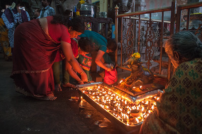 Women light diya candles to Nandi the bull.