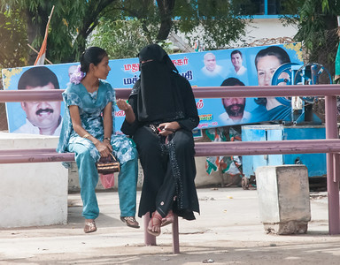 Two women of different religions chat at a bus stop.
