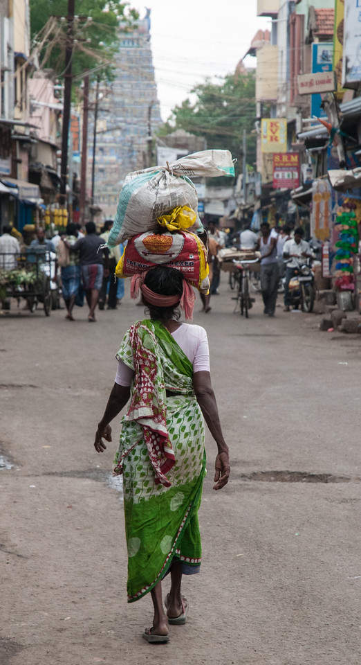 A woman carries her wares down the street toward the temple.