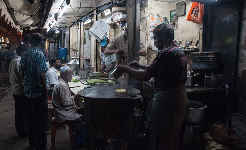 A streetcorner cafe in Madurai. The patron at left looks expectantly while the cook at right is pouring batter onto a hot griddle.  Not sure I'd eat here ;-) but it looked popular and cheap.