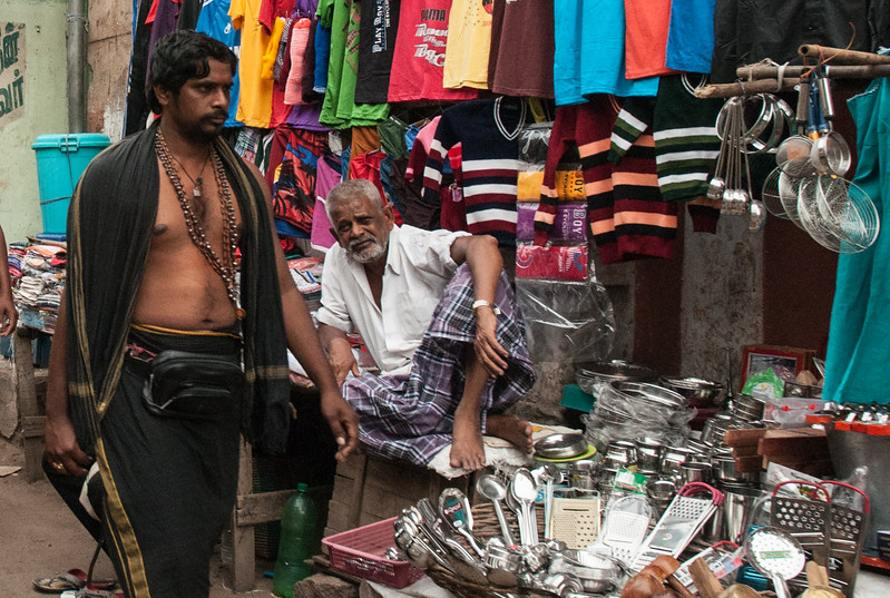 A devotee heads to the Meenakshi temple to worship – we saw dozens of men dressed alike – here passing a street vendor.