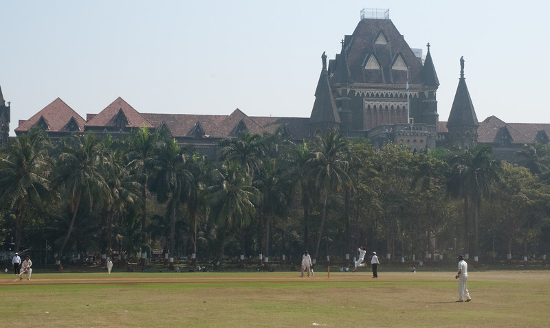 A cricket match underway on the Oval Maidan, in front of the High Court. Note the bowler about to throw the ball.
