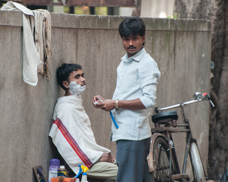 A barber and his customer pause to look at the tourist with a camera.