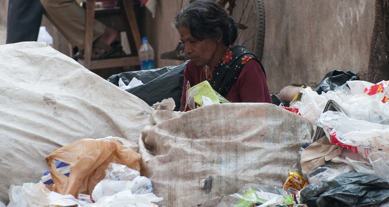 A ragpicker sorts through the sidewalk trash, pulling out recyclables she can sell.