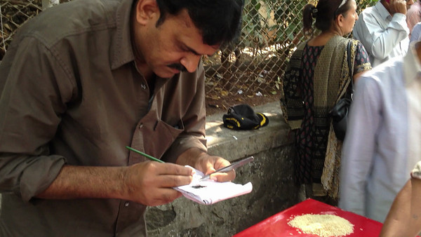 A video of a street artist painting tiny letters on a grain of rice; on this piece I believe he wrote two names.