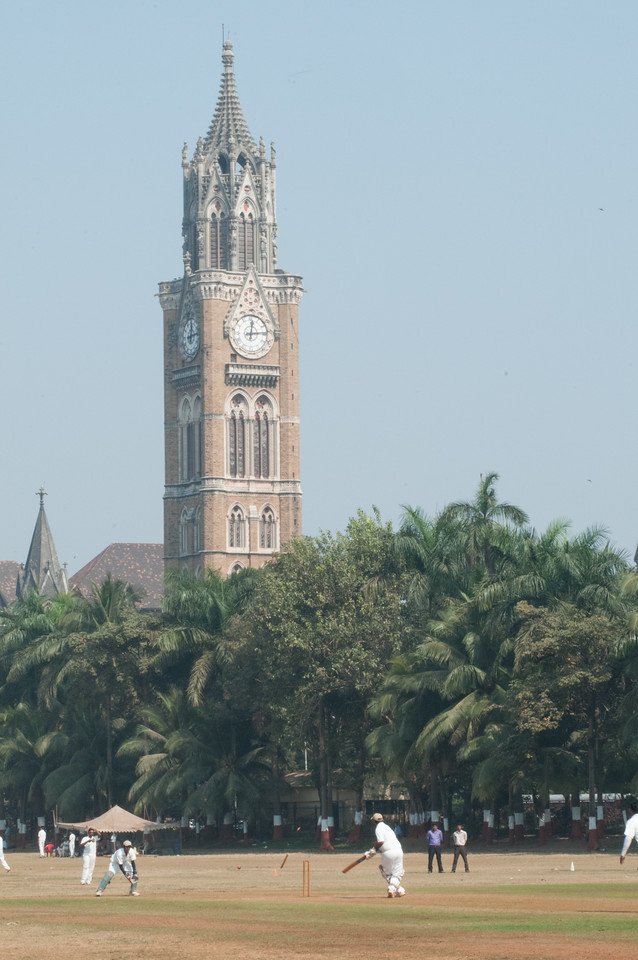 Cricket match under the watchful eye of Rajabai Clock Tower. Note the batsman missed and the ball has just knocked out a wicket.