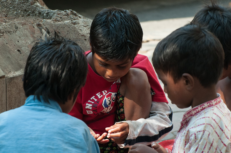 These children were sitting on the sidewalk, playing with wax from a candle, squealing and laughing like kids anywhere…