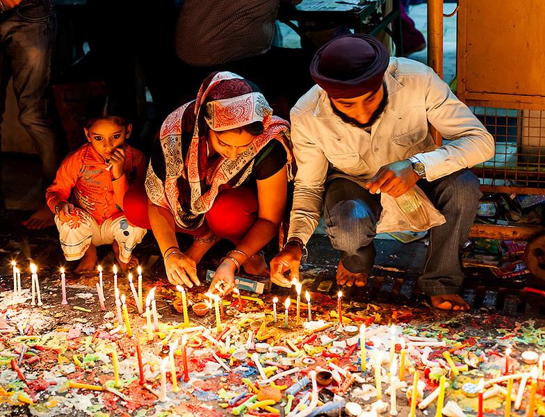 Family lighting candles during Diwali, Festival of lights. Chandni Chowk, Delhi.