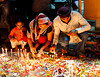 Family lighting candles during Diwali, Festival of lights. Chandni Chowk, Delhi.
