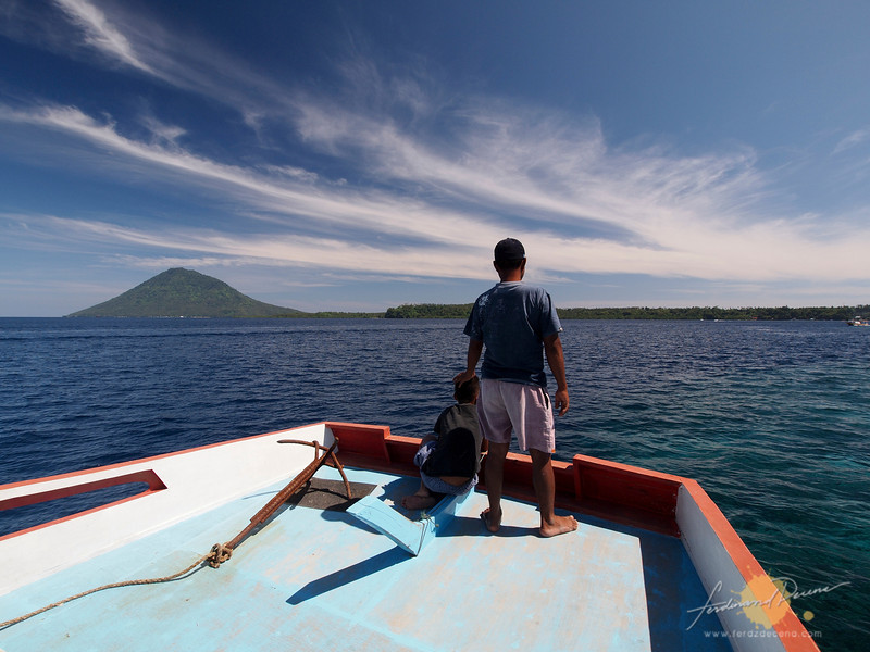 Approaching Bunaken Island with the inactive Manado Tua Volcano rising on the horizon.