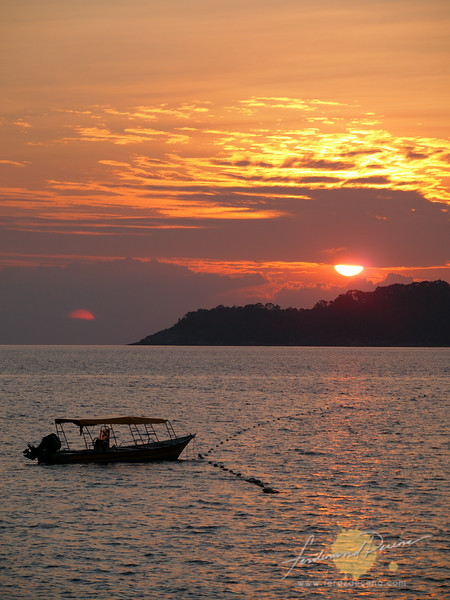 The sun peeking among the clouds over Perhentian Besar