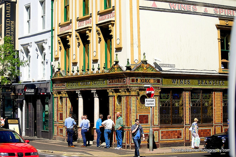 Originally opened by Felix O'Hanlon and known as The Railway Tavern, the pub was then bought by Michael Flanagan. Flanagan's son Patrick renamed and renovated the pub in 1885.<br /> The Crown owes its elaborate tiling, stained glass and woodwork to the Italian craftsmen whom Flanagan persuaded to work on the pub after hours. These craftsmen were brought to Ireland to work on the many new churches being built in Belfast at the time. It was this high standard of work that gave the Crown the reputation of being one of the finest Victorian Gin Palaces of its time.<br /> In 1978 the National Trust, following persuasion by people including Sir John Betjeman, purchased the property and three years later completed a £400,000 renovation to restore the bar to its original Victorian state. Further restoration by the National Trust was done in 2007 at a cost of £500,000. This work is the subject of a BBC Northern Ireland documentary entitled Jewel in the Crown first screened early 2008.<br /> A recognisable landmark of Belfast, the pub has featured as a location in numerous film and television productions, such as David Caffrey's Divorcing Jack (1998) and as far back as Carol Reed's 1947 film Odd Man Out.<br /> The Crown has been given a Grade A Listed Building status by the Environment and Heritage Service.