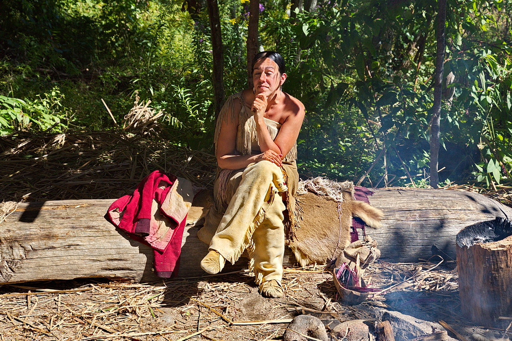 4354 A Native-American woman sits in native dress by her fire.