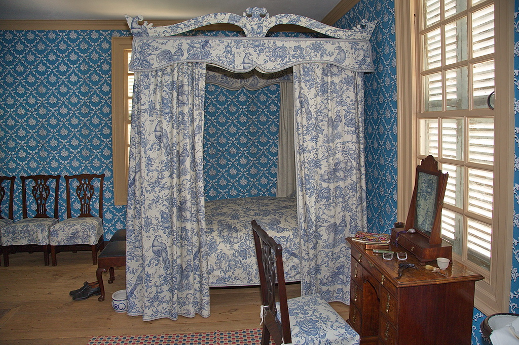 82 Here is a view of a beautifully decorated, well-to-do lady's bedroom, with draped, four-poster bed, dressing table, and jewelry box with mirror.