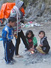 Kids warming themselves over a garbage fire