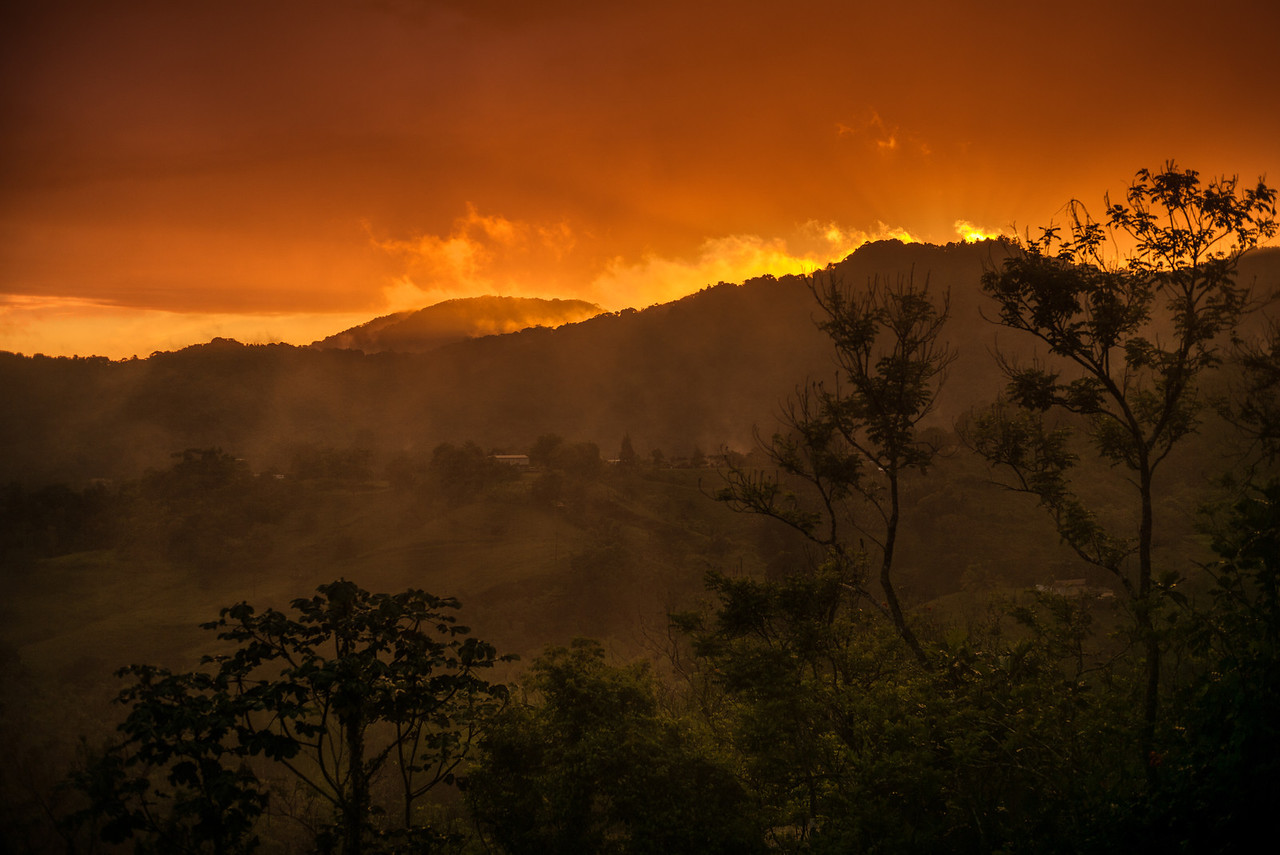 Fire in the sky...<br /> A firey sunset illuminates the post-rain mist on the mountainsides in Puerto Rico.