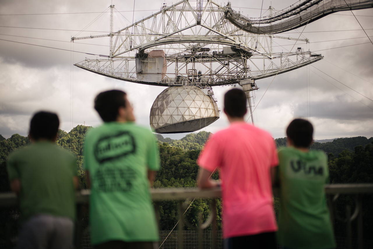 4 boys look at the massive receiver above the Arecibo Observatory reflector in Puerto Rico.