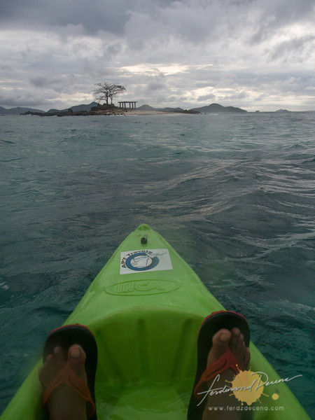 My sun-kissed feet on the kayak approaching the island