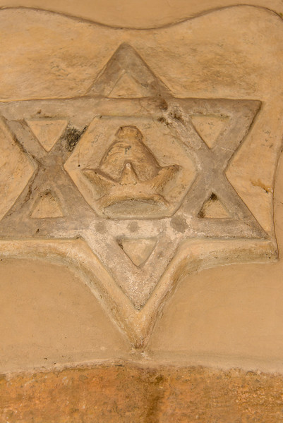 """This symbol was emblazoned on the side of a building.  It represents the Jewish insignia that they had to wear in Medieval Times.  The little hat in the center was part of their """"uniform""""."""