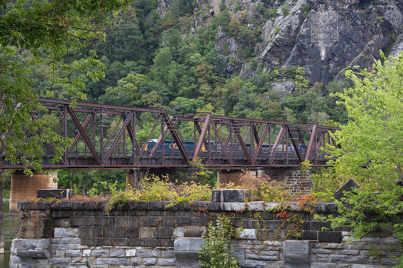 """321 A CSX freight train has come through the tunnel in Maryland and now heads west on the southern of two railroad bridges over the Potomac into West Virginia. The old, washed-out sign on the mountain used to read, """"Mennen's Borate Talcum Toilet Powder."""" It dates from the early 1900's."""