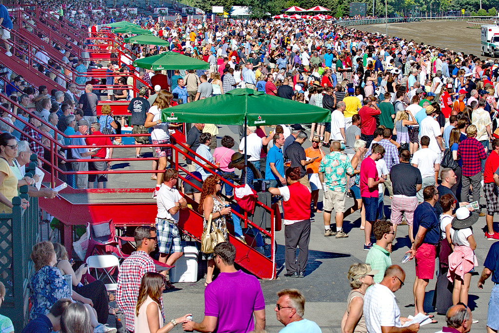 714 Late summer is high time at Saratoga Race Course in Saratoga Springs, NY, where flats and trotter races are held on three different horse tracks. Hotels, motels, and restaurants are booked solid for the period from mid-July through September 1. This photo is of only part of the crowd. Here are some of the people in the grandstands and on the apron, and there are just as many behind me by the finish line. And there are more people under the grandstands, where they watch the races on large-screen TV's.