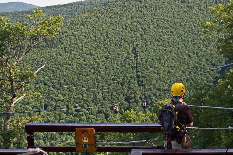"""254 Hunter's zip line has five stages. Here we see two folks starting across the first stage, which is a 3,200-foot ride from mountain top to mountain side, 600 feet above the valley below. This leg takes a minute to cross, and one can attain speeds of 50 mph. We were told the cost for the full ride is $120, includes instruction as well as zipppppppping, and takes about three hours for the full program. You can see a video here; just scroll down past the stills to the video: <a href=""""http://www.ziplinenewyork.com/photos-videos-sky.html"""">http://www.ziplinenewyork.com/photos-videos-sky.html</a>"""