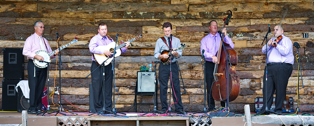 "153 The next day (a Friday) we went to ""Bluegrass in Greenville,"" a bluegrass festival in Greenville, NY (pop. 3,739). It was a three-day festival, so the ""crowd"" was small but the music was still good. Here is Remington Ryde playing a gig. The fiddler on the right was awesome on ""Orange Blossom Special,"" one of my favorite bluegrass songs."