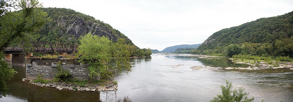 "329-335 I end with another panorama of two rivers. This view is from ""The Point"" in Harpers Ferry. The Potomac River comes in from under the railroad bridge on the left, the Shenandoah River comes in from the right (you can see some ripples this side of the rocks, and the Potomac continues straight ahead toward Washington, D.C., the city of lies, obfuscation, and cover-ups. We don't know anyone there, we don't want to know anyone there, so we didn't go there."