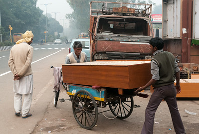 Two men load a cargo rickshaw with new furniture to be delivered. (New Delhi)