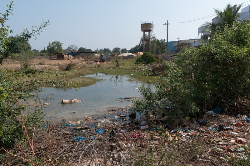 Village of Rajballaram - the village water supply (in the tank) and a pool of standing water and trash (in front).