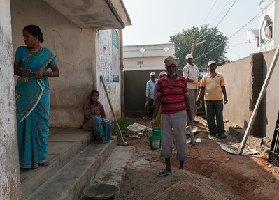 Workers pause while repairing the courtyard of a children's center. Village of Rajballaram, near Hyderabad.