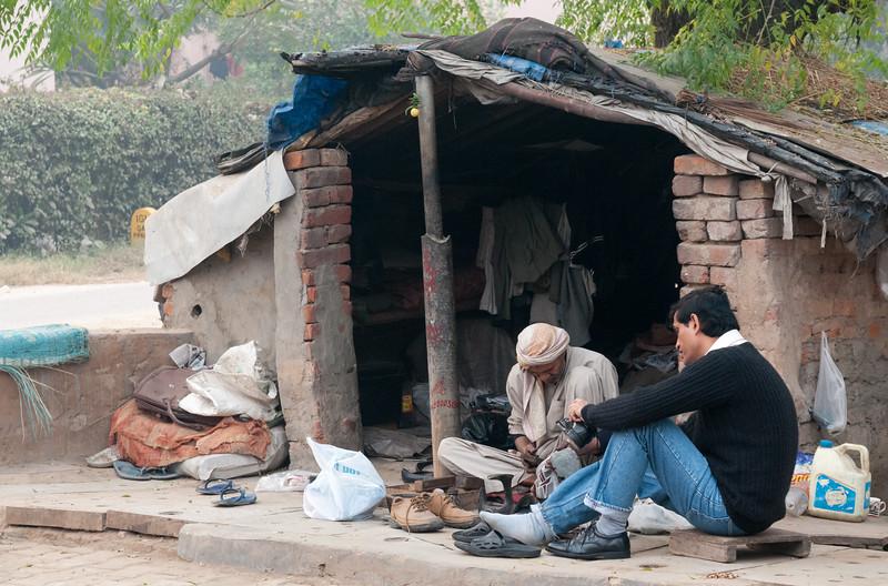 A sidewalk shoe-repair business, New Delhi.