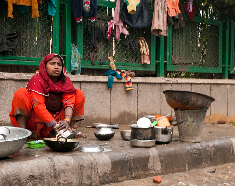 A woman washing dishes along the street in southwest New Delhi.