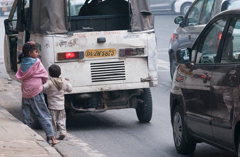 Two children beg from cars stopped at a streetlight in New Delhi.