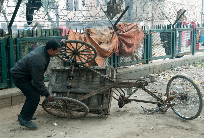 A man rights his old rickshaw after another repair. (New Delhi)