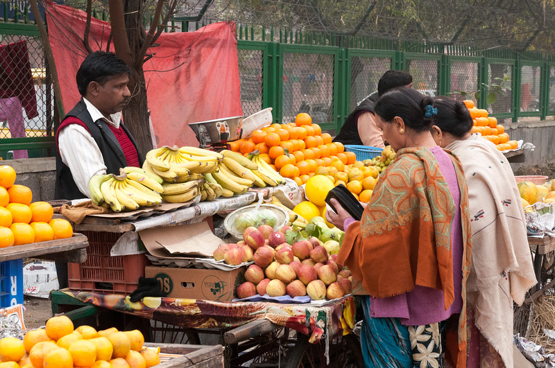 Women buying fresh fruit on a Sunday morning in New Delhi.