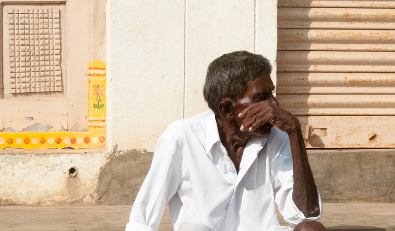 A man rests along the the street in the village of Rajballaram, near Hyderabad.