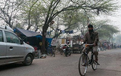 A man bicycles down a back road in southwest New Delhi.
