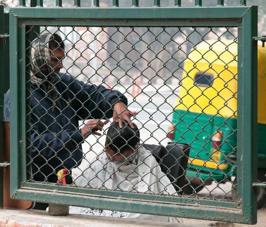 A boy's sidewalk haircut is framed by the fence. (New Delhi)