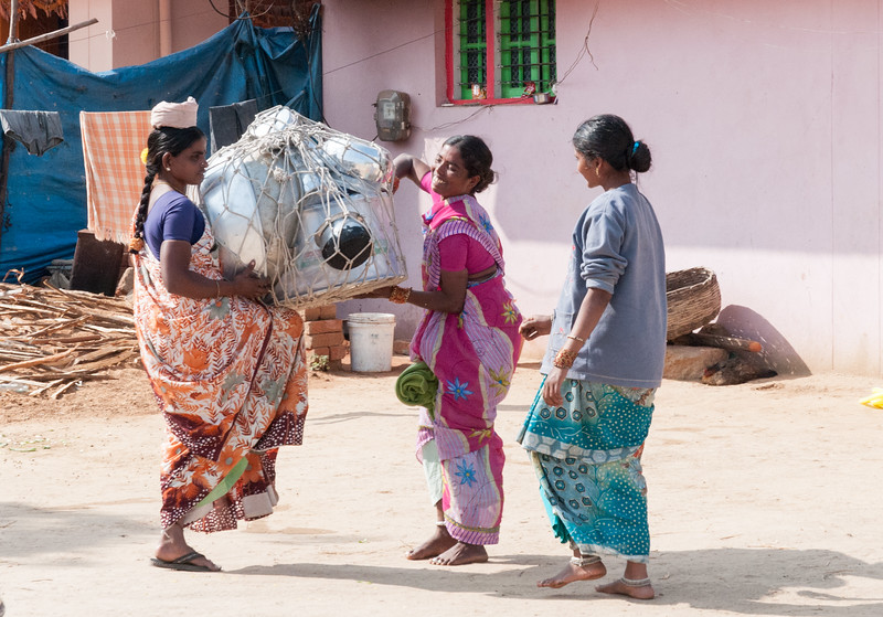 A door-to-door pot saleswoman is assisted by her customers. Village of Rajballaram, near Hyderabad.